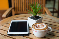 Tablet pc and coffee cup on wooden table Stock Photos