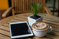 Tablet pc and coffee cup on wooden table Stock Images