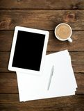 Tablet PC coffee and paper. On wooden table Royalty Free Stock Images