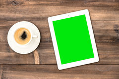 Tablet pc and coffee on wooden desk. Working station home office Royalty Free Stock Images