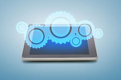 Tablet pc with cogwheel icon over screen Stock Photo