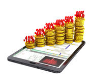 Tablet pc and columns of gold coins. Stock Photography