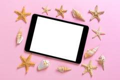 Tablet pc com as conchas do mar no fundo cor-de-rosa conceito dos feriados das férias da tecnologia foto de stock