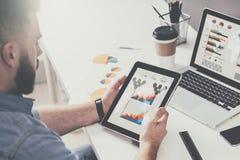 Tablet pc com gráficos, diagramas e cartas na tela nas mãos do homem de negócios farpado novo que senta-se na tabela Foto de Stock