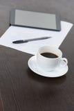 Tablet pc com xícara de café e pena na tabela Fotografia de Stock