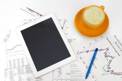 Tablet pc, cup of coffee and paper with graphs Stock Image