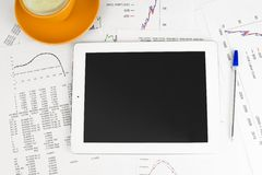 Tablet pc, cup of coffee and paper with graphs Royalty Free Stock Image