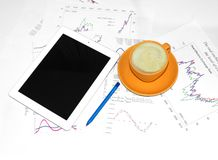 Tablet pc, cup of coffee and paper with graphs Royalty Free Stock Photography