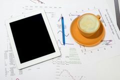 Tablet pc, cup of coffee and paper with graphs Stock Images