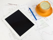 Tablet pc, cup of coffee and paper with graphs Royalty Free Stock Images