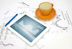 Tablet pc, cup of coffee and paper with graphs Royalty Free Stock Photo