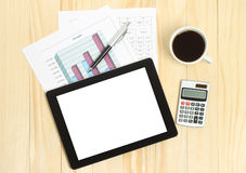 Tablet pc, cup of coffee and paper with graphs Stock Photography