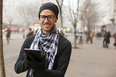 Tablet pc da eu-almofada do holdin do homem na rua Fotografia de Stock