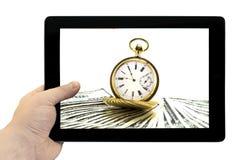 Tablet-PC in der Hand mit antiker Golduhr auf einem Stapel Gelddollarhintergrund Lizenzfreies Stockfoto