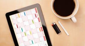 Tablet-PC, der Kalender auf Schirm mit einem Tasse Kaffee auf einem d zeigt Lizenzfreie Stockfotografie