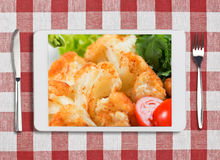 Tablet pc with dish, fork and knife on red checked tablecloth Stock Photo