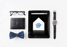 Tablet pc with e-male message and personal stuff. Technology and objects concept - tablet pc computer with e-male message icon, wallet, eyeglasses, bowtie and Stock Image