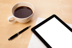 Tablet pc with empty space and a cup of coffee on a desk royalty free stock images