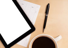 Tablet pc with empty space and a cup of coffee on a desk Stock Image