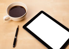 Tablet pc with empty space and a cup of coffee on a desk Royalty Free Stock Photography