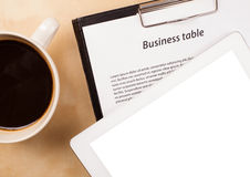 Tablet pc with empty space and a cup of coffee on a desk Stock Photo
