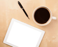 Tablet pc with empty space and a cup of coffee on a desk Stock Images