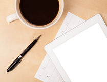 Tablet pc with empty space and a cup of coffee on a desk Royalty Free Stock Photo