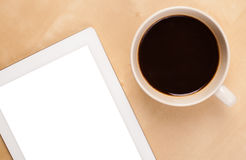 Tablet pc with empty space and a cup of coffee on a desk Stock Photography