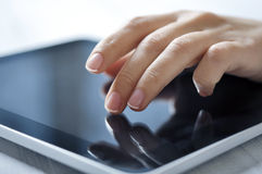 Tablet-pc and female hand. Closeup of finger touching screen on tablet-pc with shallow depth of field Stock Photos