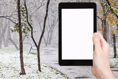 Tablet pc and first snowfall in public garden Stock Photo