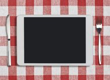Tablet pc, fork and knife on red checked Royalty Free Stock Photos