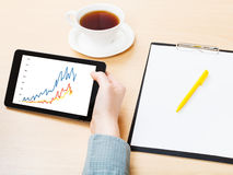 Tablet PC with graph on screen at office table Royalty Free Stock Photography