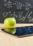 Tablet pc and green apple in front of blackboard on wood table Stock Image