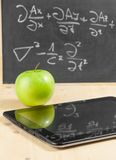 Tablet pc and green apple near blackboard Royalty Free Stock Images