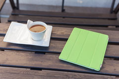 Tablet pc in green cover and cup of tea on wooden table. Relax c Stock Photos