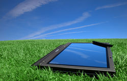 Tablet PC on green grass. Tablet PC placed on a green grass under blue sky. Cloud reflection visible on the screen. Digital pen visible in the upper right Royalty Free Stock Photos