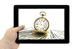 Tablet PC in hand with antique gold watch on a stack of money dollars background Royalty Free Stock Photo