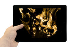 Tablet PC in hand with flames of burning fire background on screen isolated Stock Image