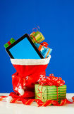 Tablet PC with heap of presents in red bag Stock Image