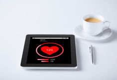 Tablet pc with heart rate icon and cup of coffee Royalty Free Stock Photos