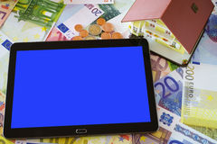Tablet PC and a Home Ownership model. Tablet PC with blank touchscreen and a Home Ownership model on a background made of Euro banknotes and coins Stock Photography