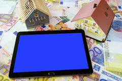 Tablet PC and a Home Ownership model. Tablet PC with blank touchscreen and a Home Ownership model on a background made of Euro banknotes and coins Stock Images