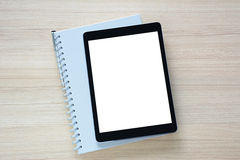 Tablet pc isolated screen with a book on wooden table Royalty Free Stock Image