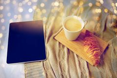 Tablet-PC, -kaffee und -hörnchen auf Bett zu Hause Lizenzfreie Stockfotografie