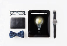 Tablet pc with light bulb icon and personal stuff Stock Images