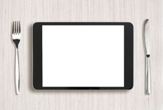 Tablet pc on light wooden table with fork and Stock Images