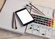 Tablet-PC mit Aquarellfarben und -bürsten auf Holztisch Lizenzfreie Stockfotos