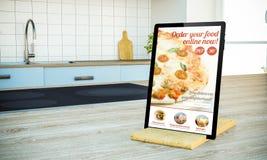 tablet PC mit Bestellungslebensmittel-on-line-Schirm auf kochender Insel an stockbild
