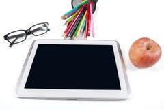 Tablet-PC mit Gläsern, Briefpapier und Apfel Stockbild