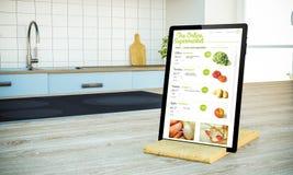 tablet PC mit on-line-Supermarktschirm auf kochender Insel an t lizenzfreies stockbild